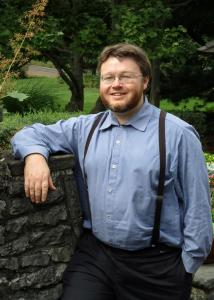 Anderson with brown hair, glasses, beard and blue shirt