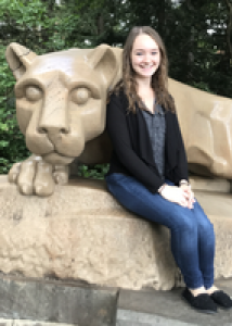 Photo of Courtnery with long brown hair, jeans, and a black blouse sitting in front of the lion shrine.