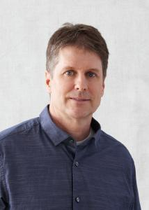 Headshot of Damon Jones, short salt and pepper hair, blue button up shirt.