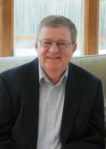 Headshot of Darrell Steffensmeier in front of a window wearing glasses with grey hair.