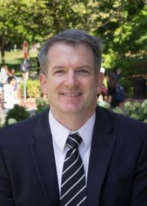 Headshot of David Conroy with grey, short hair wearing a suit and striped tie (picture taken outdoors).