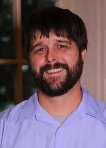 Headshot of David Ramey with dark hair and beard wearing a light purple, collared shirt.
