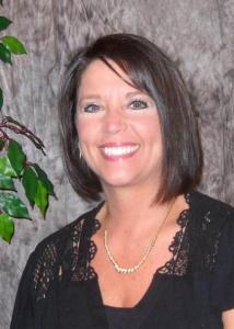 Headshot of Debra Weston with short brown hair and black dress.