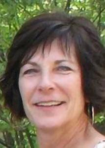 Headshot of Diane Diviney outside with mid-length hair wearing hoop earrings.