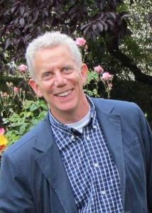 Headshot of Edward Jaenicke outside with short grey, white hair wearing blue dress shirt and suit jacket.
