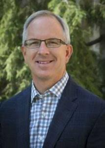 Headshot of Eric Baumer with grey, short hair wearing glasses and a blue dress shirt with a jacket.