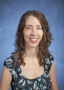 Headshot of Erica Frankenberg with long, brown and curly hair wearing a patterned top.