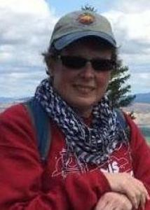 Headshot of Glenda Palmer with baseball cap, sunglasses, blue and white scarf, and red sweatshirt.
