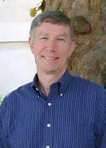 Headshot of Glenn with short gray hair and blue plaid shirt.