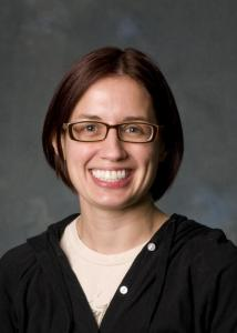Headshot of Jacqueline Mogle in front of grey background with short dark hair wearing pink top and black sweatshirt.