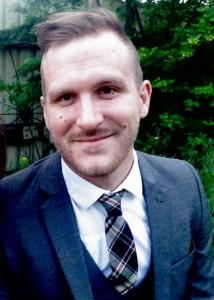 Headshot of Jason Griffin with brown hair, beard, white shirt, plaid tie, and blue jacket with vest.