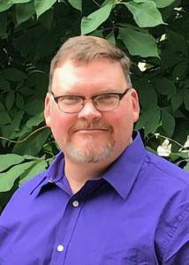 Headshot of Jeffrey Ulmer outside with short, light hair wearing a purple dress shirt and glasses.