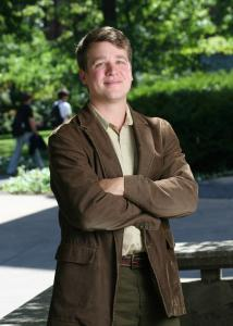 Full shot of Jeremy Staff outside with short brown hair wearing a brown suit jacket.