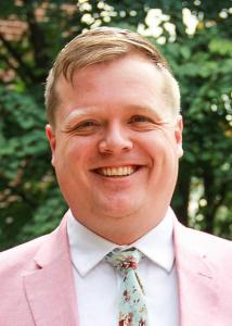 Headshot of Joel Landry outside with short, blonde hair wearing a pink suit jacket and floral tie.