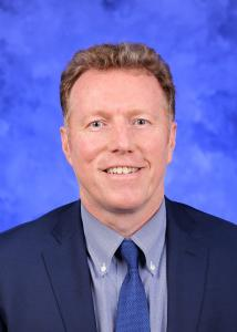 Headshot of Jonathan Foulds with short strawberry-blonde/grey hair wearing suit and tie in front of a blue background.
