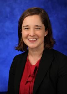 Headshot of Kristin Sznajder in front of blue background wearing red shirt and jacket.