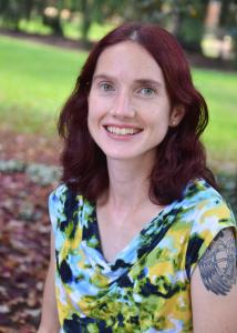 Headshot of Lacey Wallace outdoors with long red hair wearing a patterned shirt.