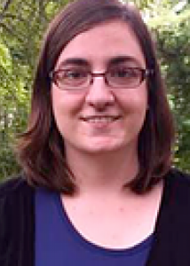 Headshot of Lawrie Green, shoulder length medium brown hair, wire frame glasses.
