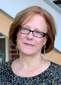 Headshot of Linda Wray with mid-length red hair wearing glasses statement earrings and patterned shirt.