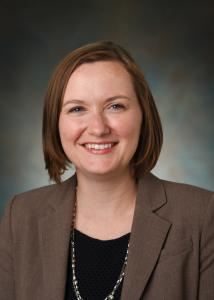 Headshot of Lindsay Fernandez_Rhodes in a grey background with mid-length, brown hair wearing a brown jacket.
