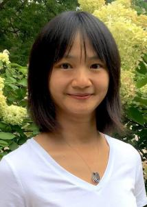 Headshot of Liying Luo outside with mid-length, dark hair and wearing a necklace and white v-neck.