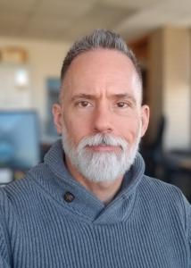 Headshot of Michael Rineer with short gray hair, full beard, and dark gray sweater.