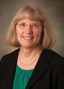 Headshot of Marianne Hillemeier with glasses and short, blonde hair wearing green shirt and black suit jacket.
