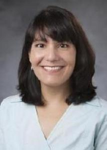 Headshot of Michele Diaz with dark brown hair and light blue blouse.