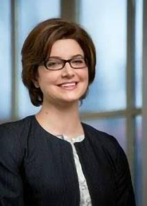 Headshot of Molly Martin with glasses and short, brown hair wearing a black jacket over a white shirt.