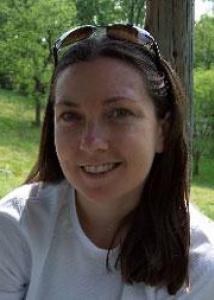 Headshot of Nancy Dennis with dark brown hair, sunglasses on her head, and white shirt.