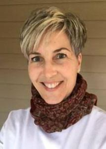 Headshot of Nancy Luke with short, blonde hair wearing a white top and brownish red scarf.