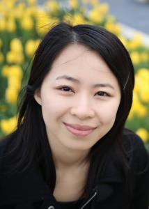 Headshot of Ni Jian with long black hair, black shirt, and yellow flowers in the background.