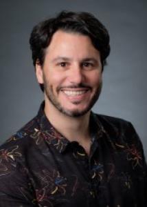 Headshot of Nicolas Sacco with black hair, beard, and black shirt with multi-colored print.