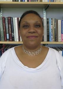 Headshot of Niki Dickerson Vonlockette in front of a book shelf wearing a white shirt and necklace.