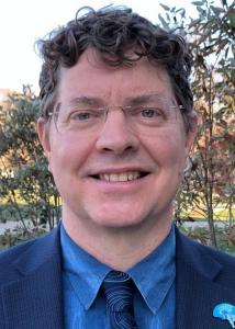Headshot of Orfeu Buxton outside in thin-rimmed, light-colored glasses wearing a blue shirt, patterned tie and dark jacket.