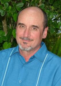Headshot of R.S. with short hair, goatee, and blue shirt.