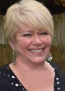 Headshot of Rachel Charney with short blonde hair wearing statement earrings and a black top.
