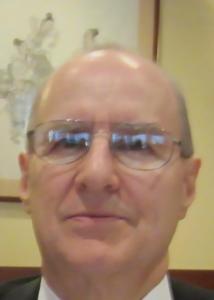 Headshot of Robert with short gray hair, glasses, white shirt, and black jacket.