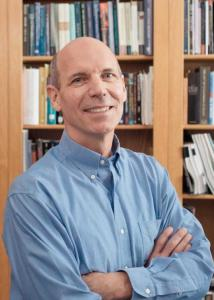 Headshot of Roger Finke in a library crossing his arms wearing a light-blue, dress shirt.