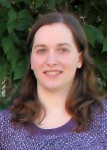 Headshot of Sarah Lemieux with long curly hair outside wearing purple top.