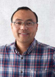 Headshot of Steven Xing, plaid button down shirt, short brown hair, and wire framed glasses.
