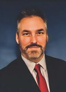 Headshot of Steven Branstetter with dark grey hair wearing a red tie and black jacket.
