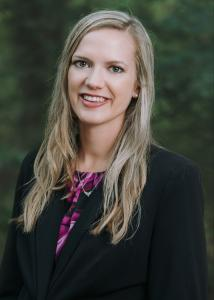 Headshot of Taylor Scott with long blonde hair, black blazer, and floral blouse.