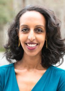 Tesfai with long dark hair and blue shirt