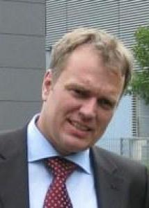 Headshot of Thomas Neuberger with light brown hair, light blue shirt, red tie, and black jacket.