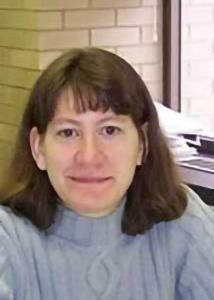 Headshot of Valarie King with mid-length, brown hair wearing a light blue sweater.