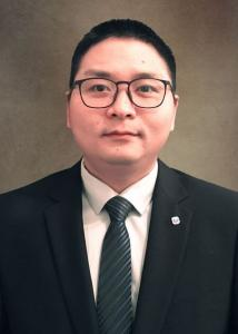 Zhou with short black hair, glasses in suit and tie