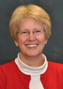 Headshot of Susan Copella with blonde hair, glasses, white turtleneck, and red sweater.