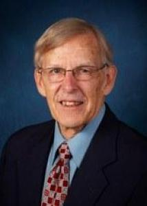 Headshot of Gordon with short gray hair, glasses, light blue shirt, red patterned tie, and dark jacket.