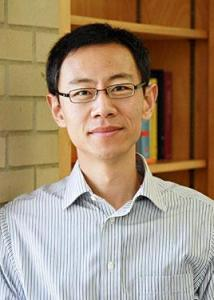Headshot of Guangqing Chi with short black hair, black rimmed glasses, wearing a blue and white striped shirt.